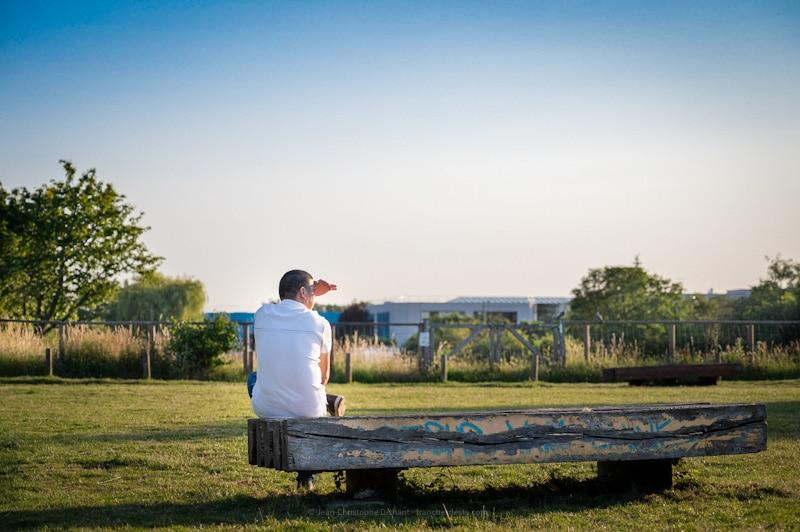Homme assis sur un banc dans le parc des Lilas à Vitry sur Seine